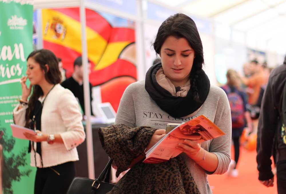 Una estudiante consultando su móvil.