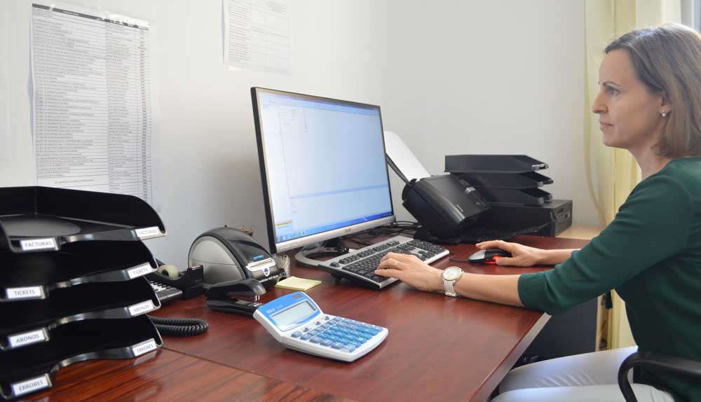 Una trabajadora de la UPCT digitalizando una factura.