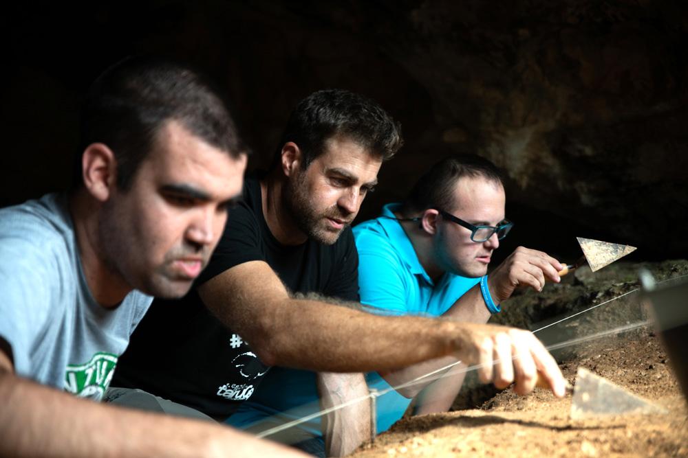Discapacitados intelectuales buscan piezas en la Cueva del Arco.